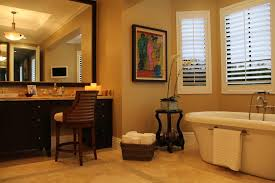 finest classy powder room design with oval shape white bathtub and cream wall color also black vanity plus large black frame wall mirror idea with luxury