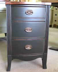 bedroom black wooden bedside table with three wooden drawer and short wooden base outstanding