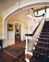 a quintessential colonial revival entrance hall is plete with a raised panel wainscot and bold