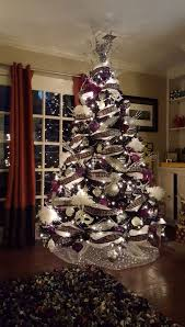 A white Christmas tree decorated with purple, black and silver deco mesh  and ornaments. To make it more dreamy, a beautiful Christmas light was  added.