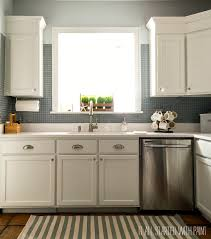 white kitchen with painted builder grade cabinets blue gray tile back splash white counter