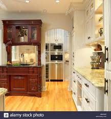 Traditional Kitchen With Cream Cabinets And Built In Dark Wood Hutch