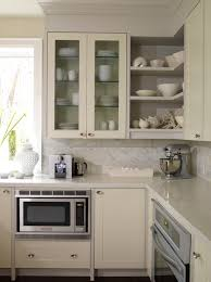 ivory kitchen design with cream glass front kitchen cabinets open shelves painted a warm gray paint color caesarstone countertoparble tiles