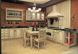 this kitchen beautifully contrasts the warm pink of the walls with the cream colored cabinetatching hardwood flooring