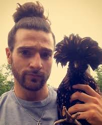 a funny man bun picture of a guy with a beard holding a bird with a