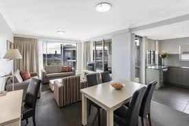apartment 3 bedroom. spacious living room area with modern furniture and large windows in bowen hills 3 bedroom apartment