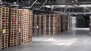 warehouse racks shelves filled cardboard boxes wrapped foil wooden pallets stock