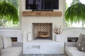 a white brick living room fireplace is accented with a chunky rustic wood mantel fixed beneath a flat panel television