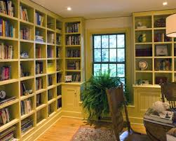 Elegant medium tone wood floor home office photo in Philadelphia with white  walls