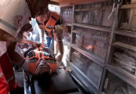 mee met de ambulance in de westelijke jordaanoever vice medici laden een vrijwilliger met een fluorescerende oranje jas in de ambulance nadat hij door twee rubberen kogels werd geraakt in zijn been