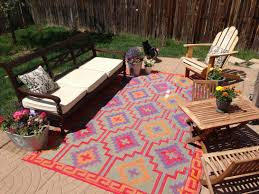 habitat colorful motives recycled plastic outdoor rugs furniture bold brown wooden sofa backyard patio natural tile floor flower pots accent green grass