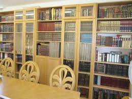 large light brown wooden books shelves with glass doors and storage on the middle combined with