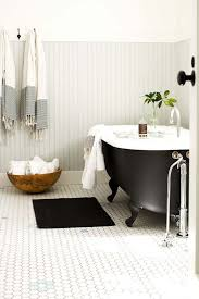 a black clawfoot bathtub with black legs makes this bathroom chic
