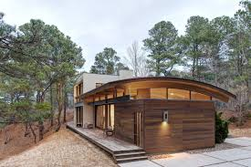 contemporary forest house with curved metal roof rooftop plans natural materials responds surroundings modern blueprints small flat houses dormer one story