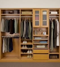 favored brown hardwood built in cabinetry as clothes organizer added frosted doors as well as shoes racks in small walk in closet design ideas