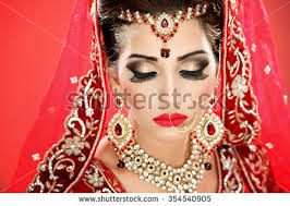 portrait of a beautiful female model in traditional indian bridal costume with jewellery and makeup