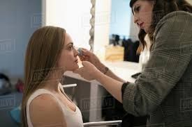 female makeup artist applying makeup to model preparing for photo shoot