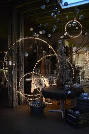 spray paint hula hoops black string lights on them and hang them from the ceiling at diffe heights design