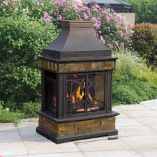 smart standalone outdoor wood burning fireplace with closed hearth and upper funnel in backyard flower garden