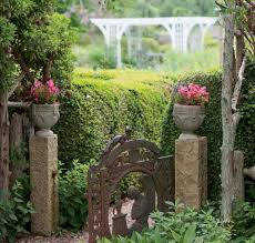 stone acres side gate is flanked by colorful nias in urns as rambling roses