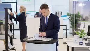 4k portrait of friendly smiling financial adviser at customer help desk in the bank shot