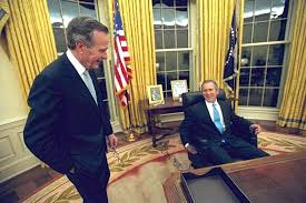 george w bush sitting at his desk in the oval office with his father bush library oval office