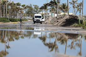 city workers inspect the dania beach parking lot which has been shut down for three days due to flooding and tons of sand flowing into the parking area as