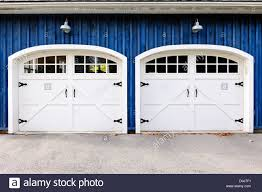 Zwei Weiße Garagentore Und Fenster Im Blauen Haus Stockfoto Bild