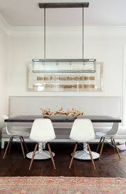 eames molded plastic dining chair. contemporary dining room with glass and iron pendant over black top table surrounded by eames molded plastic dowel leg side chairs paired chair e