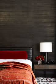 The master bedroom in a Manhattan apartment adds a pop of color in a dark  room by adding red bedding into the mix.