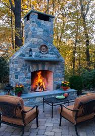 custom outdoor fireplace with fire burning inside