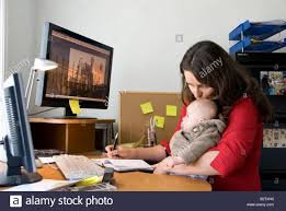home office work. Multitasking Woman Working Mother Juggles Work In Home Office And Looking After Baby Sitting On Her Knee