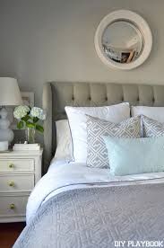 the blue decorative pillow is a nice accent to the grays and whites in the bed