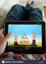 Man playing Angry Birds game on an iPad touch screen tablet computer Stock  Photo - Alamy