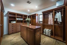 bedroom closet with brown cabinetry and hardwood flooring white walls and ceiling looks perfect together