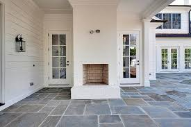 fantastic covered patio features a white brick outdoor fireplace porch floor covering