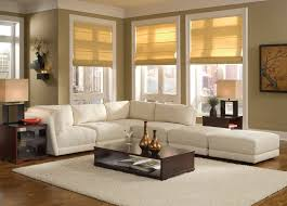 white velvet fabric apartment size sectional sofa with integrated ottoman and brown wooden coffee table on white fur rug accent