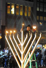rabbi mendel blecher of the woodlands lights the menorah during the chabad of the