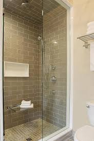 walk in shower with gray glass tiles and glass fold down shower bench