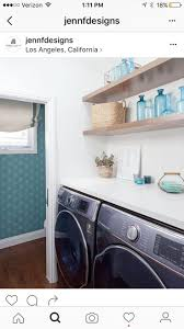 A chic laundry room boasts a vaulted ceiling with skylight placed over  brown stacked floating shelves suspended over a black front load washer and  dryer ...