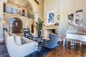 the formal living room features a white couch in front of a fireplace and has a