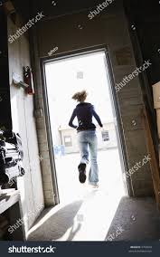 woman running through open door from building to sunny outside