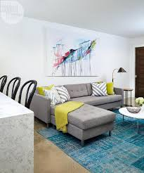 contemporary basement family room boasts a large colorful abstract canvas art piece hung on white walls above a gray tufted sectional topped with citron