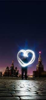 man forrming heart light iPhone X ...