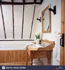 washstand bathroom pine: basin in pine washstand in small white beamed attic bathroom with pine panelled bath
