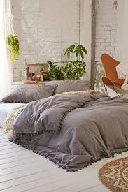 grey pom fringe duvet cover retro leather chair green ferns in a white room the bohemian haven