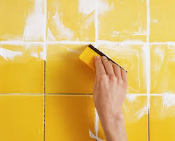 grout being applied to tiles using a grout spreader