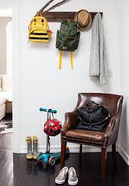 A reclaimed coatrack adds instant functionality to a blank wall by the  entry. The leather