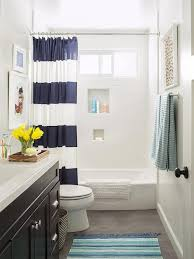 lovely kid s bathroom features a black sink vanity topped with contrasting white quartz countertop alongside a blue striped bath mat layered on gray slate