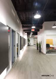 Black Ceilings corridor in an office space with black laminate accent wall with 1939 by xevi.us